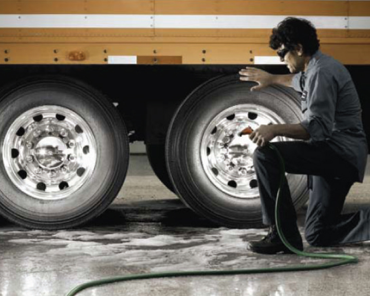 Image of man kneeling by truck wheels